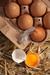 Box of fresh farm eggs with an egg yolk