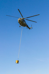 Helicopter in action carrying the water bucket.