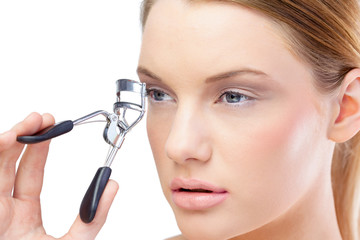 Attractive blonde model using eyelash curler