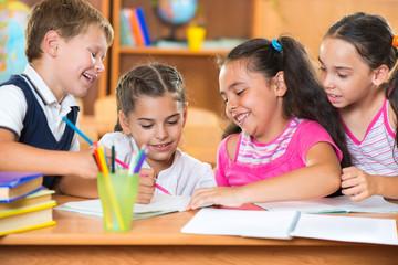 Group of cute schoolchildren having fun in classroom