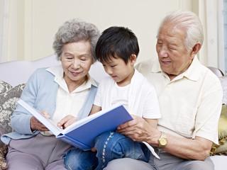 grandparents and grandson reading book together