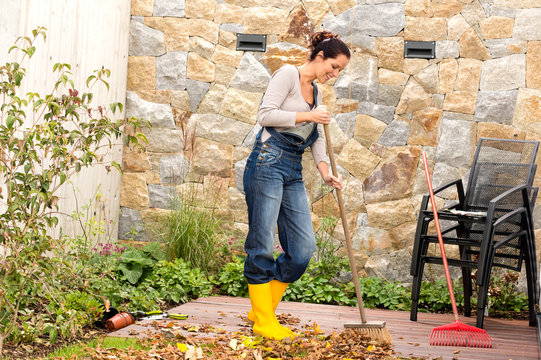 Young woman sweeping autumn leaves veranda