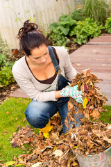 Young woman autumn gardening cleaning leaves