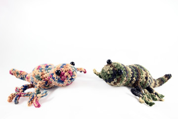 Two handcrafted toy geckos crocheted from colorful yarns.
