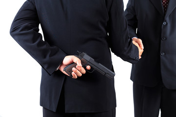 Businessman hiding gun while handshaking concpet for dishonesty