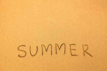 Summer, text written by hand in sand on a beach.