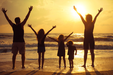 Happy family standing on the beach on the dawn time