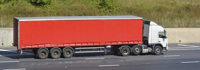 White truck with red articulated trailer on motorway