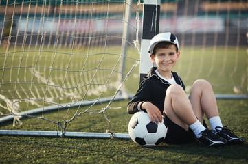 Little boy plays football on stadium