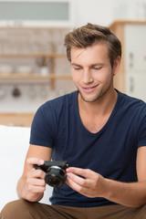 mann schaut fotos auf seiner digitalkamera