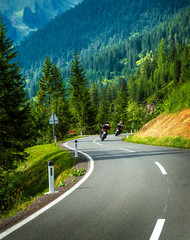 Fototapete - Group of motorcyclists in Alpine mountains