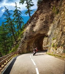 Fototapete - Biker riding into mountainous tunnel