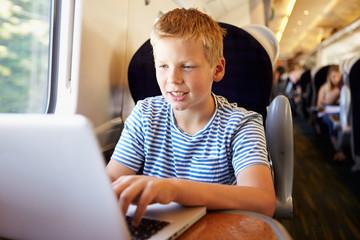 Boy Using Laptop On Train Journey