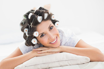 Pretty brunette in hair rollers lying on her bed smiling at came