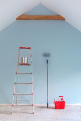 Paint tools against a newly painted blue wall