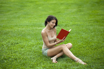 Young beautiful young woman reading a book outdoor