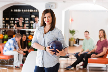 Confident Young Woman With Bowling Ball in Club