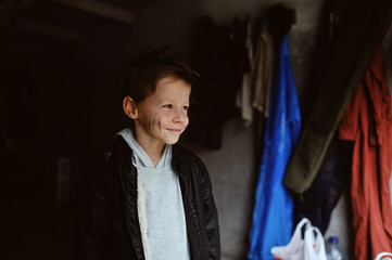 portrait of a mischievous boy with a dirty face in a black jacke