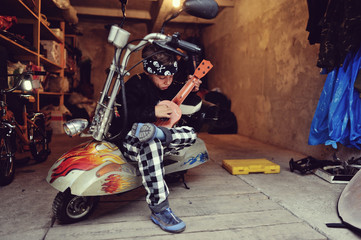in the garage of a boy with dirty face and a moped with a guitar