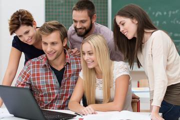 studenten schauen gemeinsam auf laptop