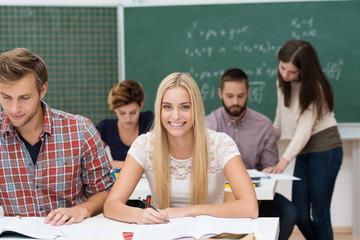 lächelnde studentin sitzt im seminarraum