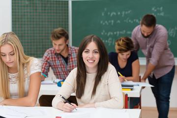 lächelnde studentin schreibt mit im seminar