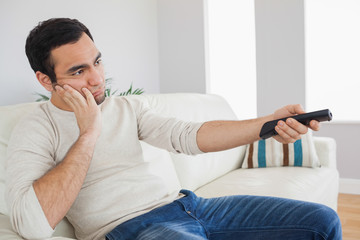 Handsome man getting bored of tv programs