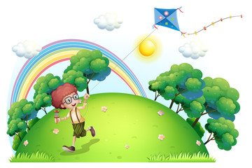 A boy playing with his kite at the hilltop