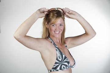 Woman in bikini holding sunglasses