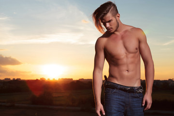 topless man looks down at sunset