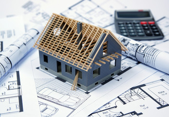 house under construction with ground plan and calculator