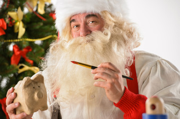 Authentic Santa Claus holding piggy bank and painting it