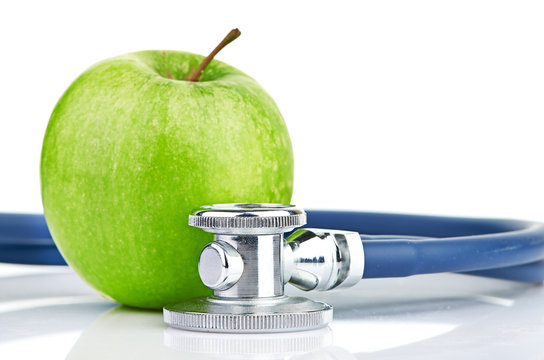 Medical stethoscope and apple isolated on white