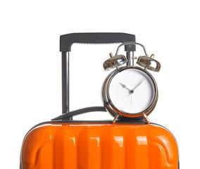 Alarm clock on orange suitcase