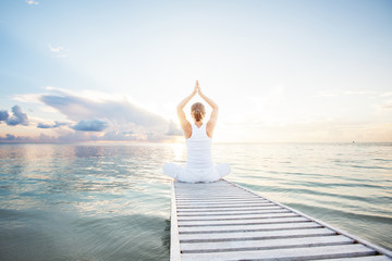 Tuinposter Ontspanning Caucasian woman practicing yoga at seashore