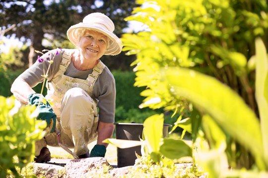 Happy elder woman working in her garden