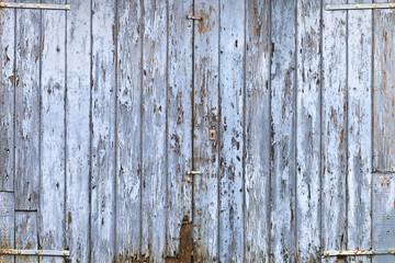 Old, grunge wood panels of wide light blue door