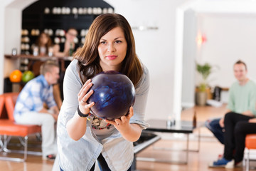 Young Woman Ready With Bowling Ball in Club
