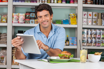 Male Customer With Snacks Using Digital Tablet In Supermarket