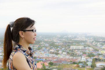 Women look at a view of the city from on high.