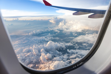 Clouds and sky as seen through window of an aircraft at sunset