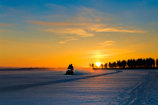 Orange sunset on winter snowy lake and snowmobile with people
