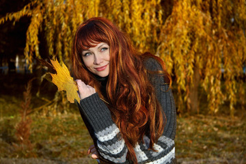 girl with red hair, in autumn park.