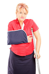 Injured mature woman with broken arm and crutch