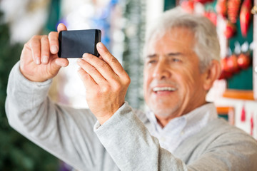 Man Photographing In Christmas Store
