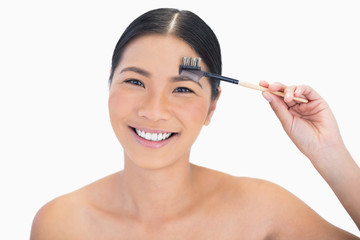 Smiling gorgeous natural model using eyebrow brush