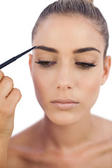 Thoughtful woman applying make up on her eyebrows