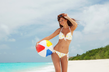Young pretty woman with ball on the beach background