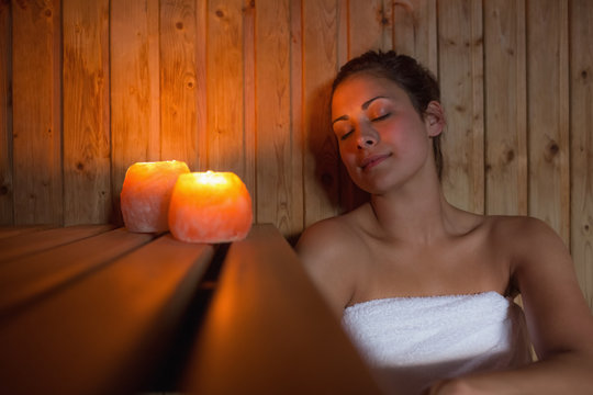 Happy brunette woman sitting in a sauna