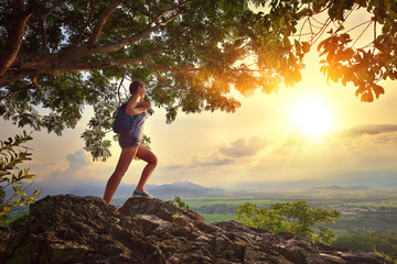Young woman admires the sunset with a backpack standing on cliff Wall mural